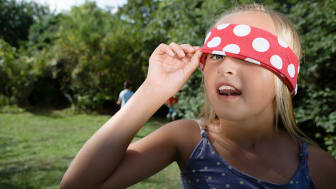 A girl peeks from under a blindfold.