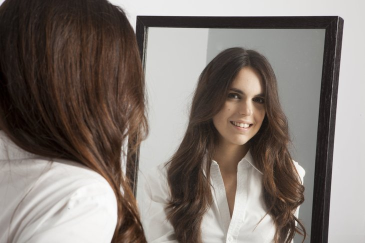 Woman looking in the mirror while trying on new clothes