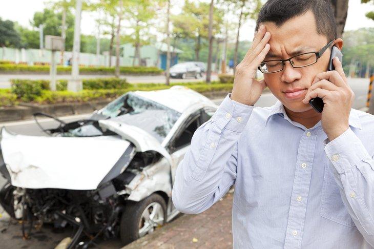 A man makes a phone call after a car crash