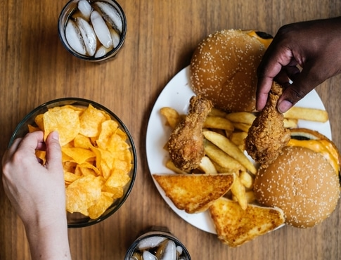 A bowl of chips and a plate of burgers, chicken, and fries