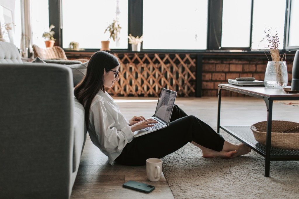 woman sitting on her computer touring homes virtually 2021 home