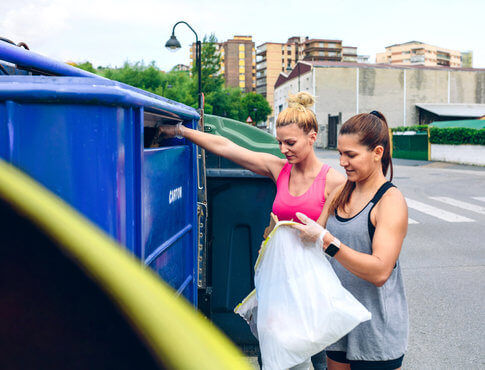 Two girls throwing stuff away in a dumpster