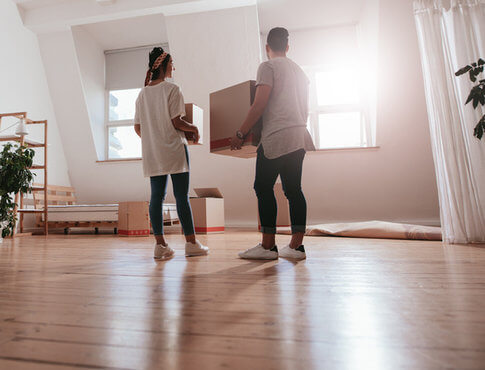 two young people moving boxes into a new apartment